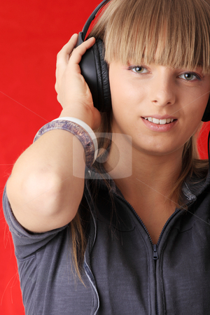 Listening to Music stock photo, Young beautiful happy women listening music in headphones   by Piotr_Marcinski