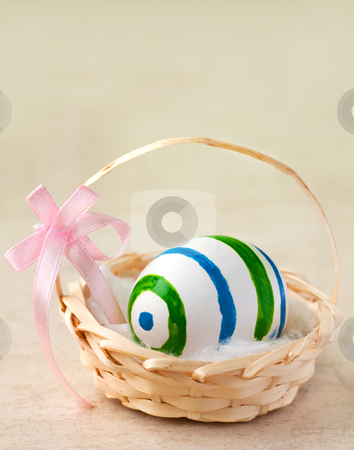 Easter egg in basket stock photo, Painted easter egg in a basket with ribbon by borojoint