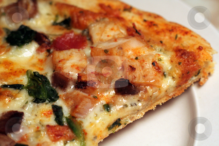 Closeup a Mediterranen Pizza stock photo, A close up of a slice of Mediterrainian pizza sitting on a plate.  by Chris Hill