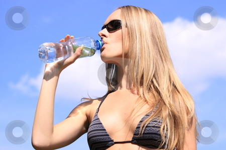 Girl drinking water stock photo, Girl drinking water against blue sky in sunny day by Piotr_Marcinski