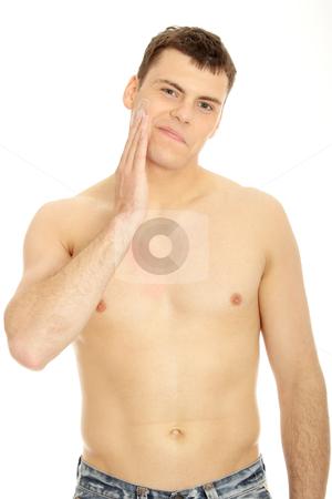 Skin care stock photo, Happy man after shaving applying moisturizing cream upon his face  by Piotr_Marcinski