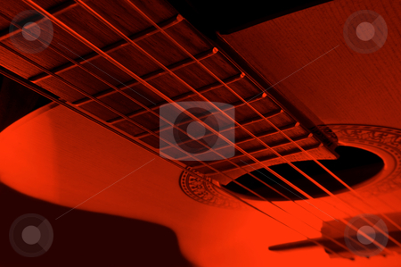Acoustic guitar stock photo, Acoustic guitar with extreme red light effect. by Samantha Craddock