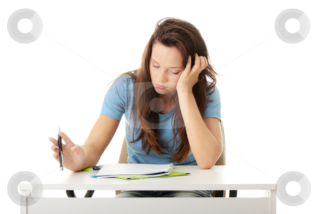 Teenage girl studying at the desk being tired stock photo, Teenage girl studying at the desk being tired, isolated on white   by Piotr_Marcinski