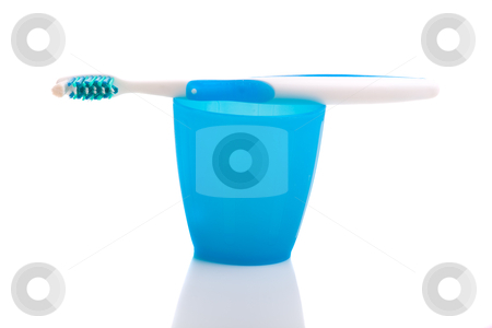 Toothbrush stock photo, Hygiene objects, toothbrush on a cup isolated on white background by ikostudio
