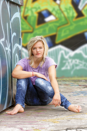 Attractive Blonde with Graffiti (3) stock photo, A lovely young blonde leans against a graffiti-covered garbage dumpster with a graffiti-covered wall behind her. by Carl Stewart