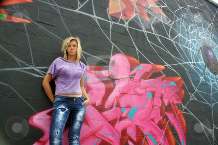 Attractive Blonde with Graffiti (10) stock photo, A lovely young blonde leans against a graffiti-covered wall.  Low angle. by Carl Stewart