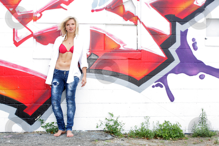 Attractive Blonde with Graffiti (11) stock photo, A lovely young blonde leans against a graffiti-covered wall. by Carl Stewart