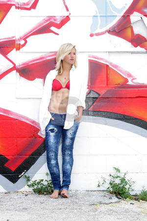 Attractive Blonde with Graffiti (12) stock photo, A lovely young blonde leans against a graffiti-covered wall. by Carl Stewart