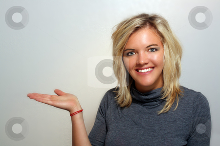 Attractive Young Blonde Hostess (1) stock photo, A studio close-up of a lovely young blonde with a bright, warm smile, holding her right hand out to frame left, palm up, pointing to your product or allowing you to place it in her hand. by Carl Stewart