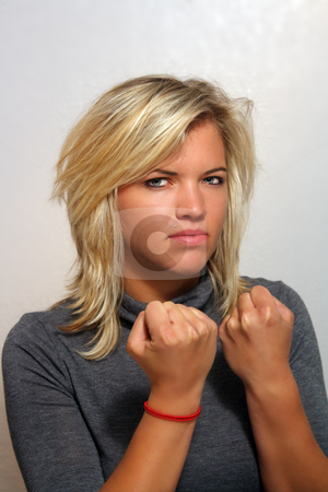 Attractive Young Blonde with Fists Clenched stock photo, A studio close-up of a lovely young blonde holding up her clenched fists, ready for a fight. by Carl Stewart