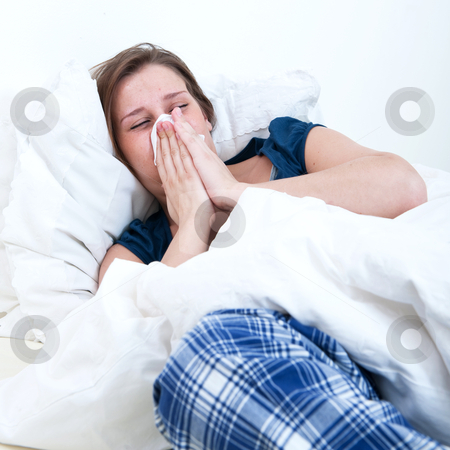 Blowing nose stock photo, A girl blowing her nose while lying sick in bed. by Corepics VOF