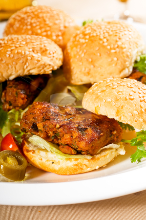 Mini chicken burgers stock photo, four fresh and delicious mini chicken burgers on a plate ,close up by Francesco Perre