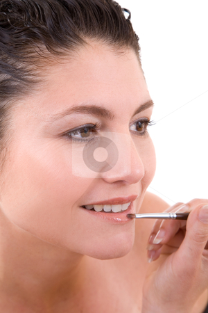 Applying lipgloss stock photo, Pretty brunette applying lipstick to her lips with a small brush on white background by Simone Van den Berg