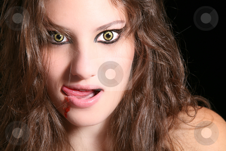 Scary woman stock photo, Scary woman with wolf eyes licking her lips by Simone Van den Berg
