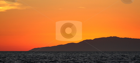 Sunset stock photo, Sunset over the ocean with an island in the background by Henrik Lehnerer