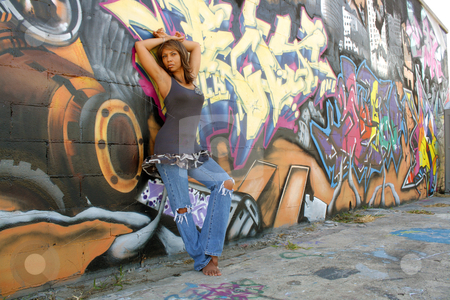 Beautiful Mature Black Woman with Graffiti (2) stock photo, A lovely mature black woman, wearing tattered jeans, stands barefoot leaning against a wall of graffiti art. by Carl Stewart