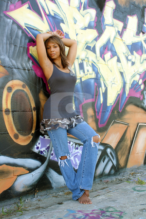 Beautiful Mature Black Woman with Graffiti (3) stock photo, A lovely mature black woman, wearing tattered jeans, stands barefoot leaning against a wall of graffiti art  by Carl Stewart