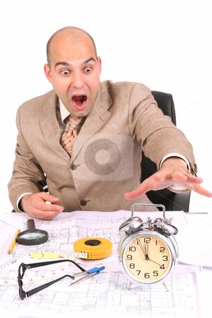 Businessman looking at clock alarm stock photo, businessman looking at clock alarm at a desk by vladacanon1