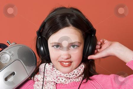 Pretty girl listening music stock photo, pretty girl listening music with headphones and holding portable CD radio by vladacanon1
