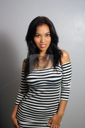 Beautiful Smiling Asian Girl (3) stock photo, A lovely young Indonesian model with long, luscious black hair, arresting brown eyes, and a bright, warm smile, wearing a black-and-white stripe tube dress. by Carl Stewart