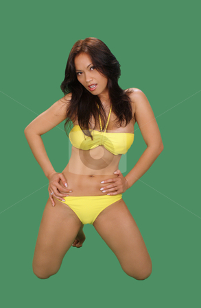 Beautiful Bikini-clad Asian Girl (1) stock photo, A lovely Indonesian model, kneeling, wearing a yellow bikini, isolated on a plain green background. by Carl Stewart