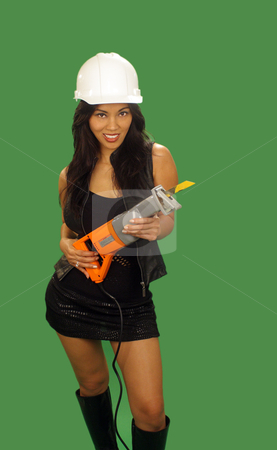Beautiful Asian Female Construction Worker (2) stock photo, A lovely young and fashionable Indonesian model with long, luscious black hair, holds a reciprocating saw, isolated on a plain green background. by Carl Stewart