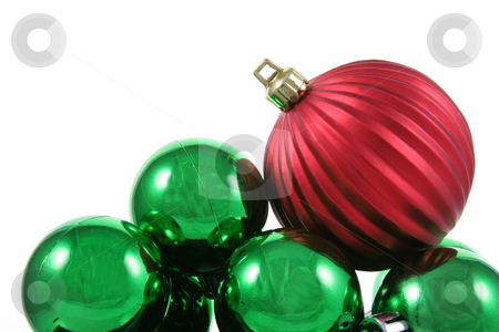 Red Bauble on Green Baubles stock photo, A red bauble sitting on a bunch of green Christmas baubles against a white background.  by Chris Hill