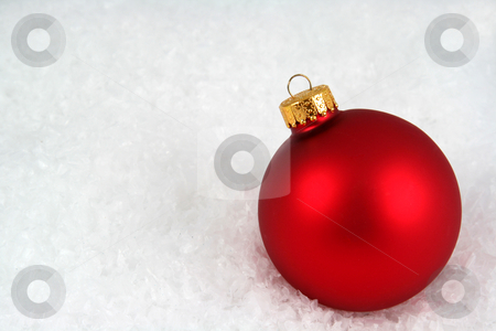 Red Christmas Bauble in the Snow stock photo, A red Christmas bauble sitting in a bed of snow.  by Chris Hill