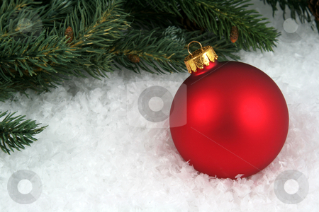 Red Bauble and Branch stock photo, A red Christmas bauble sitting in a bed of snow with an evergreen branch.  by Chris Hill