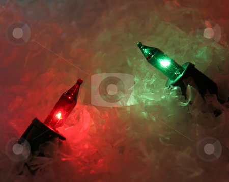 Pair of Xmas Lights stock photo, A red and green Christmas light sitting in fake snow.  by Chris Hill