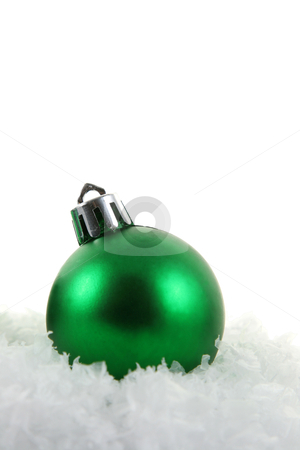 Simple Green Xmas Bauble stock photo, A green Christmas bauble sitting in a bed of snow.  by Chris Hill