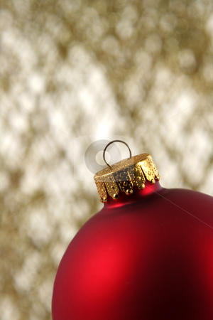 Red Bauble Closeup stock photo, A red Christmas bauble backed by gold glittery strings.  by Chris Hill