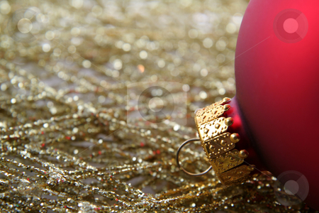 Red Bauble and Gold Wrap stock photo, A red Christmas bauble sitting on gold decorative wrap. by Chris Hill