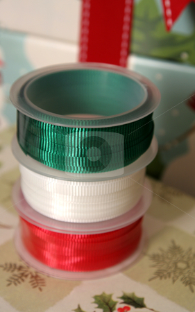Christmas Ribbon Spools stock photo, Three spools of Christmas gift wrapping ribbon sitting on already wrapped gifts.  by Chris Hill