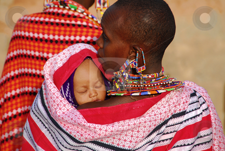 African stock photo, Masai Mara, Kenya- July, 2009:Masai mother with her child. The woman wears traditional jewelry forgings of small colored beads.  by africa