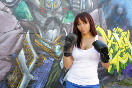 Beautiful Female Boxer (1) stock photo, A lovely young female boxer stands ready in front of colorful graffiti. by Carl Stewart