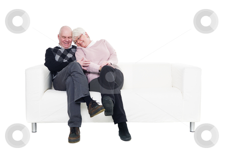 Older couple in a sofa stock photo, Older couple in a sofa isolated on white background by Anne-Louise Quarfoth
