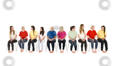 Group of women on chairs in a line stock photo, Group of Young women sitting on chairs wearing colorfull t-shirts by Anne-Louise Quarfoth