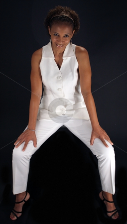 Beautiful Mature Black Woman Sitting Straddle stock photo, A lovely mature black woman sits straddle-style on a black background, allowing you to easily insert something for her to sit on or extract her from the black background to have her sitting on something. by Carl Stewart