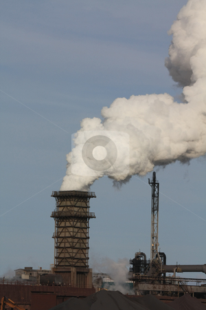 Smoking chimney in industrial area stock photo, Smoke out of a chimney in industrial area by Porto Sabbia