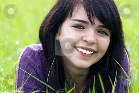 Beautiful Brunette in a Grassy Field (3) stock photo, Close-up of a lovely young brunette with a bright, warm smile lying in a field of tall green grass. by Carl Stewart