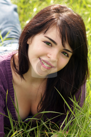 Beautiful Brunette in a Grassy Field (4) stock photo, Close-up of a lovely young brunette with a bright, warm smile lying in a field of tall green grass. by Carl Stewart