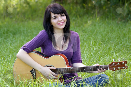 Beautiful Brunette Outdoors with a Guitar (2) stock photo, A lovely young brunette sits in a field of tall green grass with her acoustic guitar, looking directly at the camera. by Carl Stewart