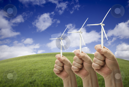 Male Fists Holding Three Wind Turbines Outside stock photo, Male Fists Holding Three Wind Turbines Outside with Grass Field, Sky and Clouds. by Andy Dean