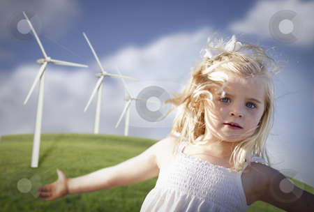 Beautiful Young Girl and Wind Turbine Field stock photo, Beautiful Young Girl Playing Near Wind Turbines and Grass Field. by Andy Dean