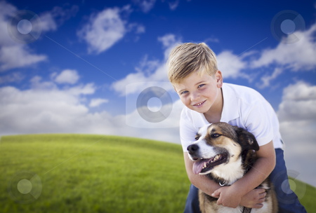Handsome Young Boy Playing with His Dog in the Grass stock photo, Handsome Young Boy Playing with His Dog on a Lush Green Grass Field. by Andy Dean