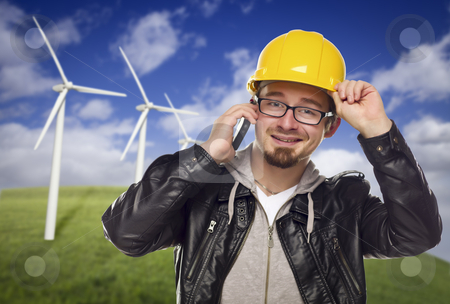 Hard Hat Wearing Engineer on Phone with Turbines Behind stock photo, Smiling Hard Hat Wearing Engineer on Cell Phone with Wind Turbines Behind Him. by Andy Dean