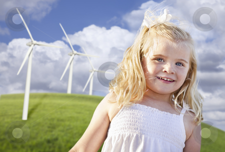 Beautiful Young Girl Playing in Wind Turbine Field stock photo, Beautiful Young Girl Playing Near Wind Turbines and Grass Field. by Andy Dean
