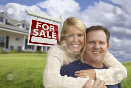 Happy Couple Hugging in Front of Real Estate Sign and House stock photo, Happy Couple Hugging in Front Yard with Real Estate Sign and House. by Andy Dean