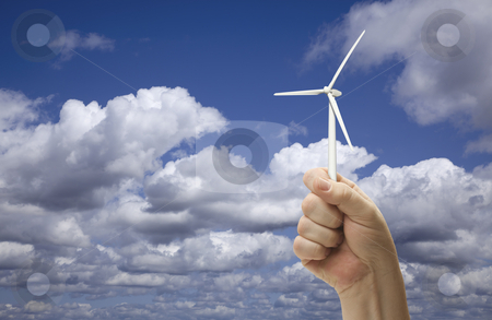 Male Fist Holding Wind Turbine Outside stock photo, Male Fist Holding Wind Turbine Outside with Clouds and Sky. by Andy Dean